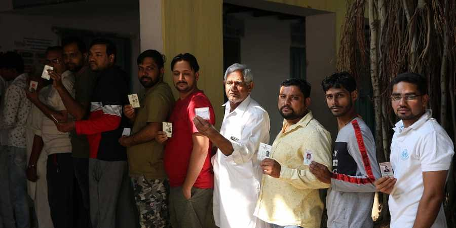 Voters wait in queues to cast their votes for Haryana Assembly elections at a polling station in Gurugram on Monday.