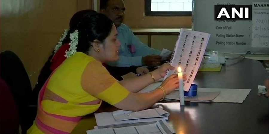 Polling officials had candles placed at their tables to help them tally voter details properly.