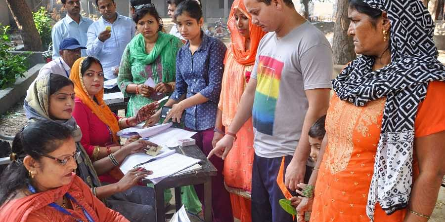 Polling officials conduct their procedure as voters wait to cast their votes at a polling station for the Haryana Assembly elections in Sonepat Monday.