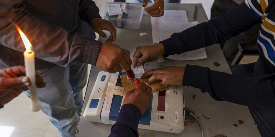 Election officials and observers seal a polling apparatus at a polling booth