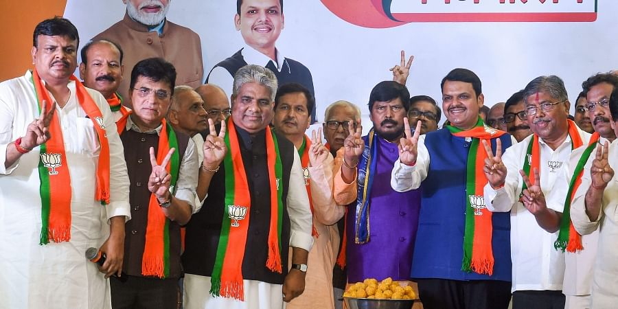 Maharashtra Chief Minister Devendra Fadnavis State BJP president Chandrakant Patil senior leader Bhupendra Yadav RPI chief Ramdas Athawale and other leaders flash victory signs as they celebrate their win in Maharashtra Assembly elections in Mumbai.