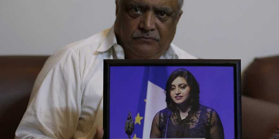 Professor Mohammad Ismail, father of a Pakistani human rights activist Gulalai Ismail, holds a picture of his daughter as he poses for a photo, in his home in Islamabad