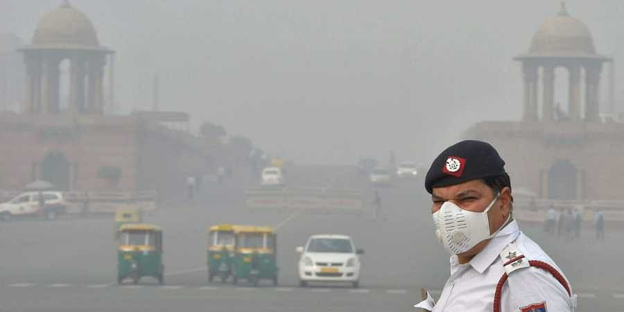 A traffic policeman wearing an anti-pollution mask mans traffic amid smog and air pollution in New Delhi.   PTI File Photo