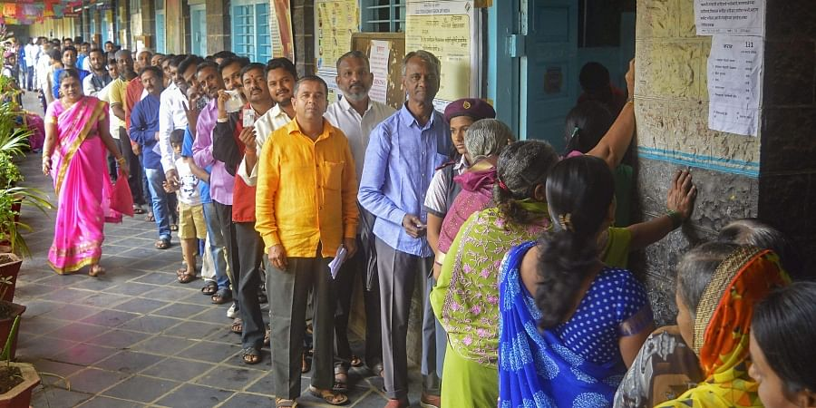 Voters stand in a queue as they wait to cast their votes at a polling station for the Maharashtra Assembly elections in Karad.