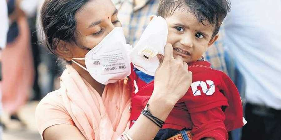 A woman puts an anti-pollution mask on a child's face, in New Delhi.