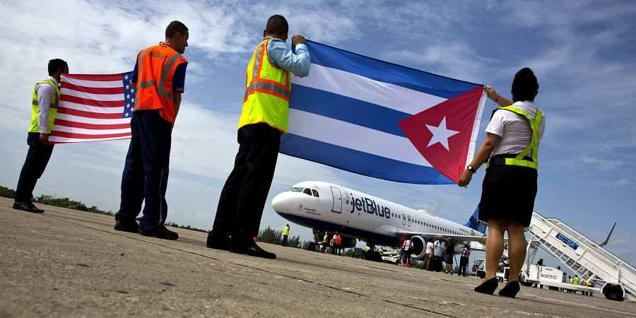 Airport workers receive JetBlue flight 387, the first commercial flight between the U.S. and Cuba in more than a half century, holding a United States, and a Cuban national flag, on the airport tarmac in Santa Clara