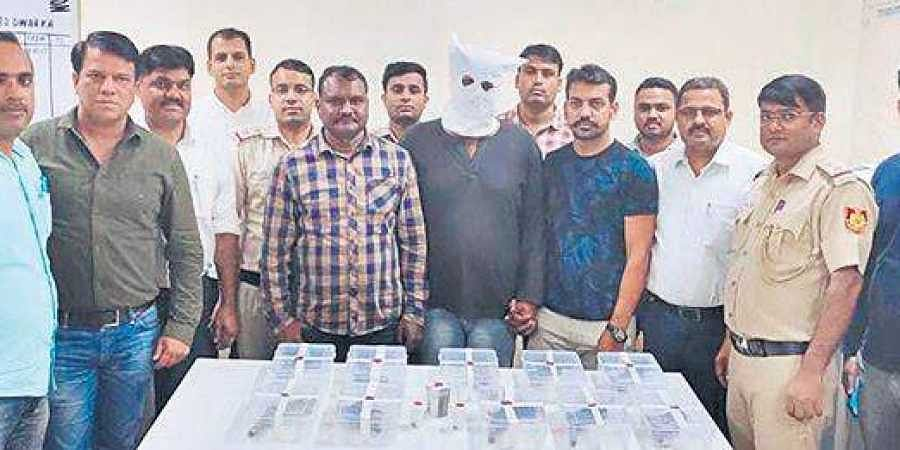 The accused (in hooded face) after being arrested on Friday. He was nabbed after a brief exchange of fire with the police in the Dwarka area.