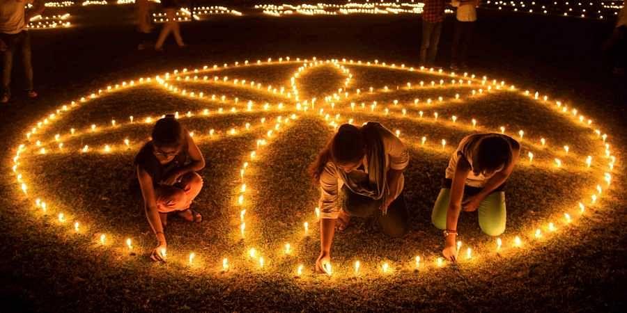 People lighting earthern lamps on the bank of river Saryu for Diwali.
