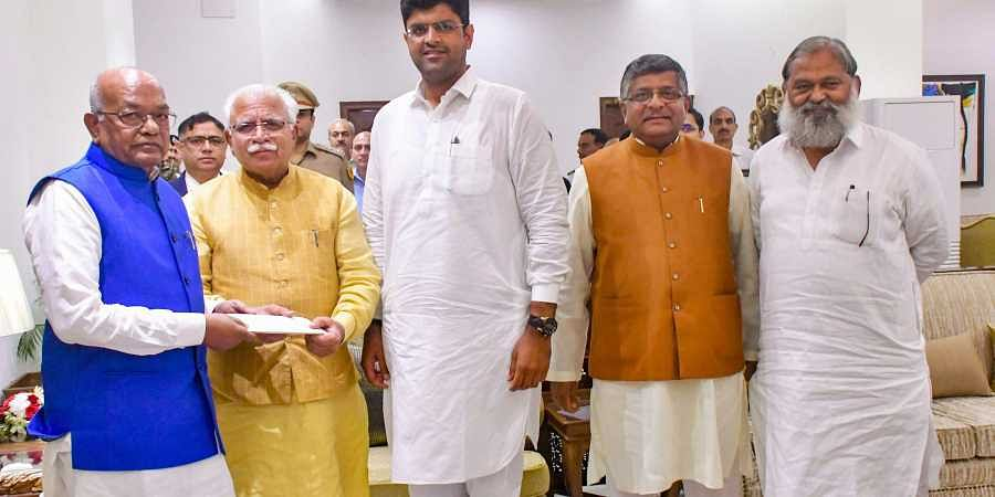 Haryana Chief Minister-designate Manohar Lal Khattar with JJP chief Dushyant Chautala meets Governor Satyadeo Narain Arya to stake claim for forming the next government in the State at Raj Bhawan in Chandigarh Saturday.