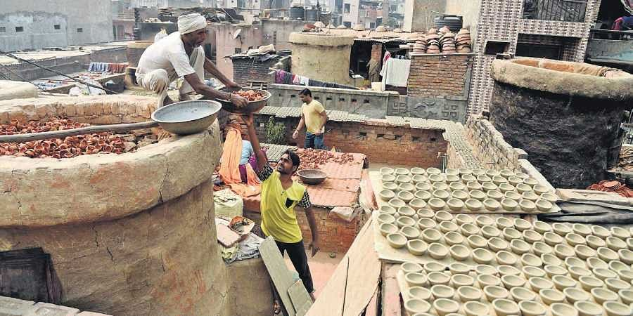 Pre-Diwali scenes at Kumhar Gram with the potter community moulding clay diyas and firing these at traditional kilns that the government wants to replace with gas furnaces.   (