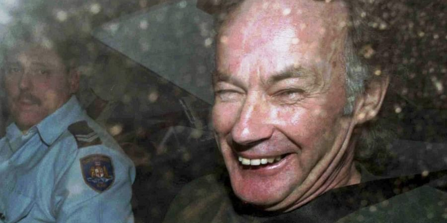 Serial killer Ivan Milat smiles in a police car after attending a court in Sydney, Australia.