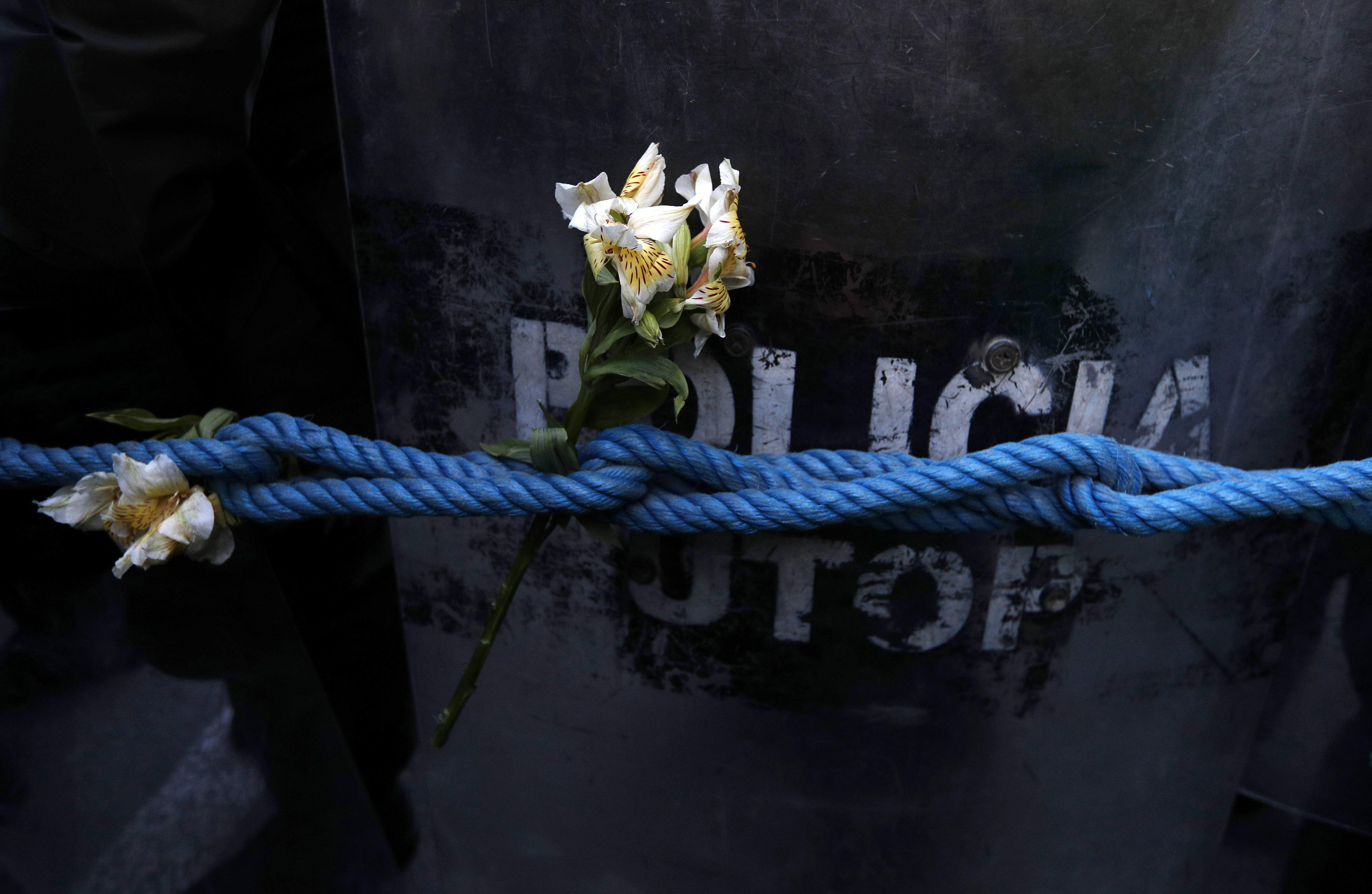 In  this photo, flowers placed by protesters can be seen on ropes which the police placed to guard the top election court where ballots are counted. Bolivia has been seeing week-long protests since President Evo Morales saw victory in an oddly delayed official quick count. The angry mob is seeking a second round of presidential election after they accused the election authorities of fraud. Bolivian officials say they're negotiating with the Organization of American States for an audit of the country's presidential election.