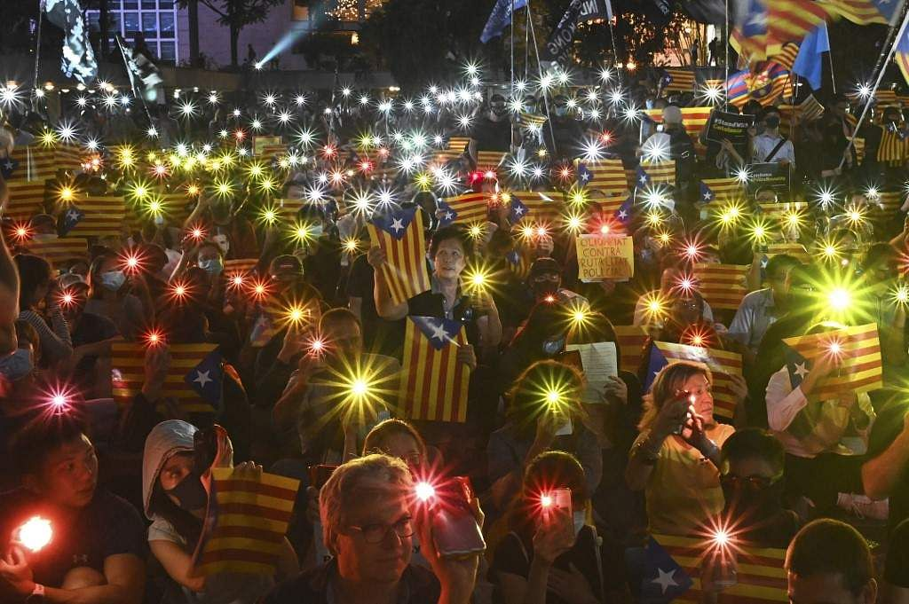 The four-month-old protest that started out for the withdrawal of a Bill that would allow extradition of criminals to China mounted to a widespread cry for democracy and police accountability. In this picture, people hold Catalan's pro-independence 'Estelada' flags and light up their mobile phones during a solidarity assembly where Hong Kongers supported Catalans on October 24, 2019. Read on to find out why Catalonia is protesting.