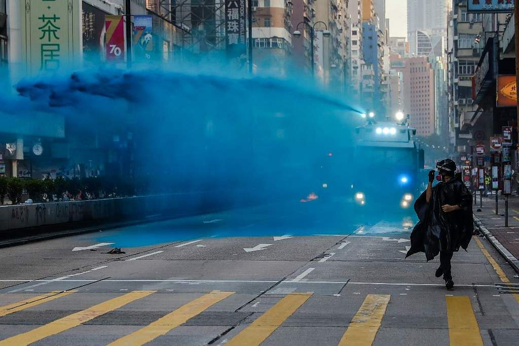 Seen in this picture is a protestor running from police as they deploy water cannon on a road in Hong Kong on October 20, 2019. Police took up extreme measures of firing water cannons and tear gas on protesters who revolted against authorities. The number of demonstrators continued to swell even after October 20, the point at which the extradition bill was scrapped, due to the recent attacks on pro-democracy protesters by Beijing supporters.