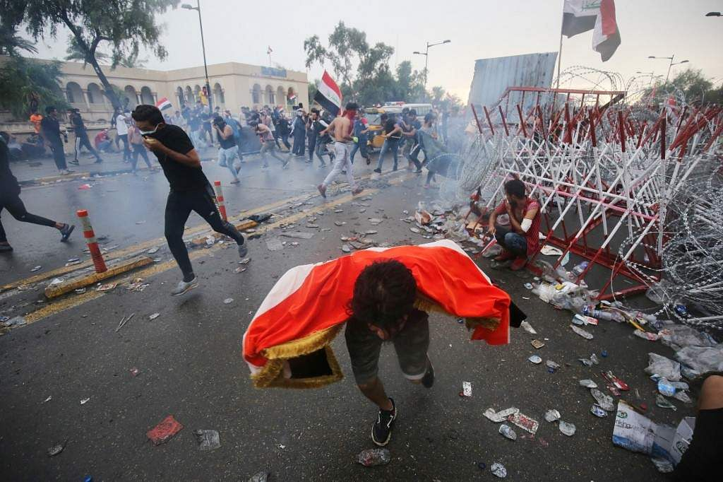 Iraqi protester is seen running for cover from teargas canisters fired by security forces during an anti-government demonstration on Al-Jumhuriya Bridge in the Iraqi capital Baghdad on October 25, 2019. More than a dozen demonstrators have died in renewed rallies across Iraq's capital, with the first reported use of live rounds in this wave of protests. The demonstrations represent a second phase of a week-long movement in early October demanding an end to widespread corruption, unemployment and an overhaul of the political system.