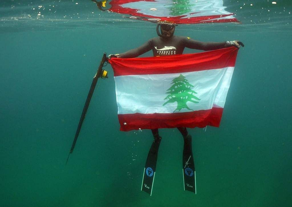 A freediver takes a Lebanese national flag with him underwater off the shore of the northern town of Qalamun in solidarity with ongoing protests across the country on their seventh day, on October 23, 2019. One of the largest protests Lebanon has seen in years were sparked by new government proposals on taxes, whatsapp voice call and messaging services but it has now has escalated into a call to overthrow the  post-civil war government viewed as corrupt and incompetent.