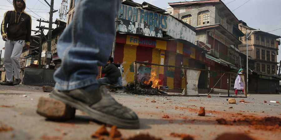 Kashmiri youth protesting against India throw bricks and make fire to block traffic on a road in Srinagar, Indian controlled Kashmir, Sunday, Oct. 27, 2019.
