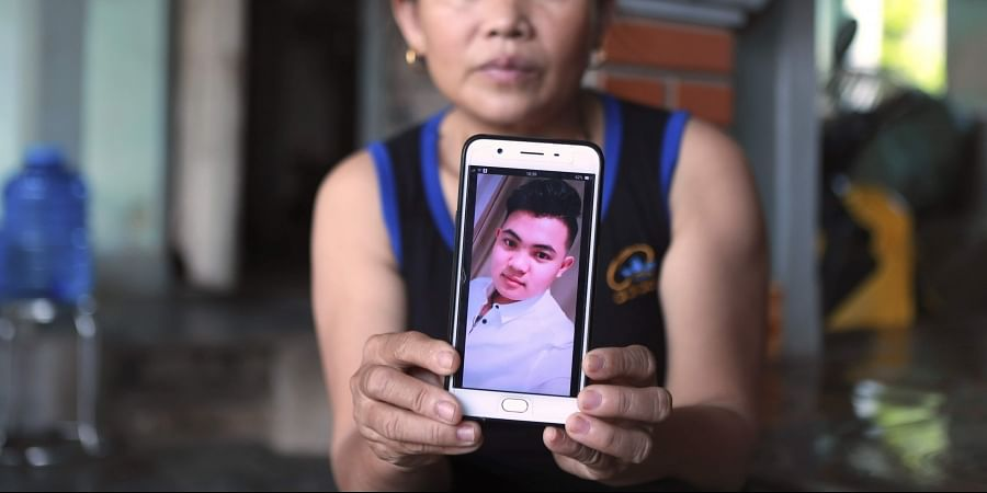 Hoang Thi Ai holds up her phone showing a photo of her son Hoang Van Tiep, who she fears is one of the possible victims in the truck deaths in England.