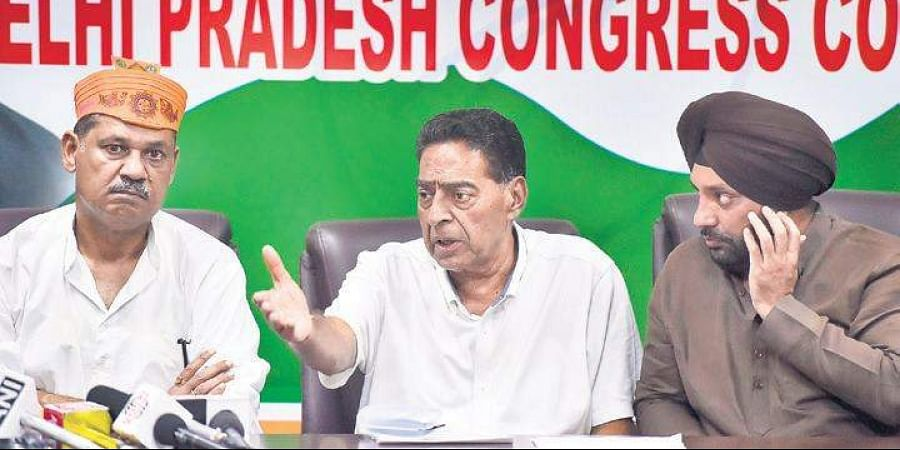 DPCC president Subhash Chopra (C), along with party leaders Kirti Azad and Arvinder Singh Lovely (R), addresses a press conference.