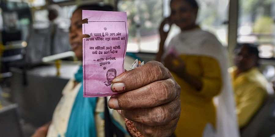 A woman shows the 'pink ticket' during her ride on a DTC Bus in New Delhi. (Photo | PTI)