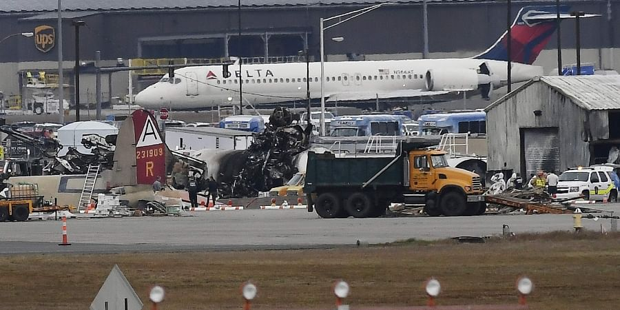 A Delta commercial airline plane taxis to take-off behind investigators at the wreckage of World War II-era bomber plane that crashed at Bradley International Airport in Windsor Locks.