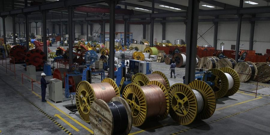 A worker monitors automatic copper wire unit at a plant