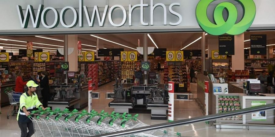A worker pushes shopping trollys at a Woolworths store in Sydney on August 25, 2016. Australian supermarket giant Woolworths on August 25 reported a large annual net loss of AUD 1.23 billion (USD 940 million), its first since listing more than two decades ago, following a failed push into hardware and a slump in food sales.
