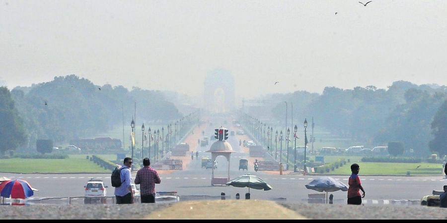 India Gate is seen faintly from Raisina Hills on Saturday morning as a nip in air and dust have started bringing smog in the national capital
