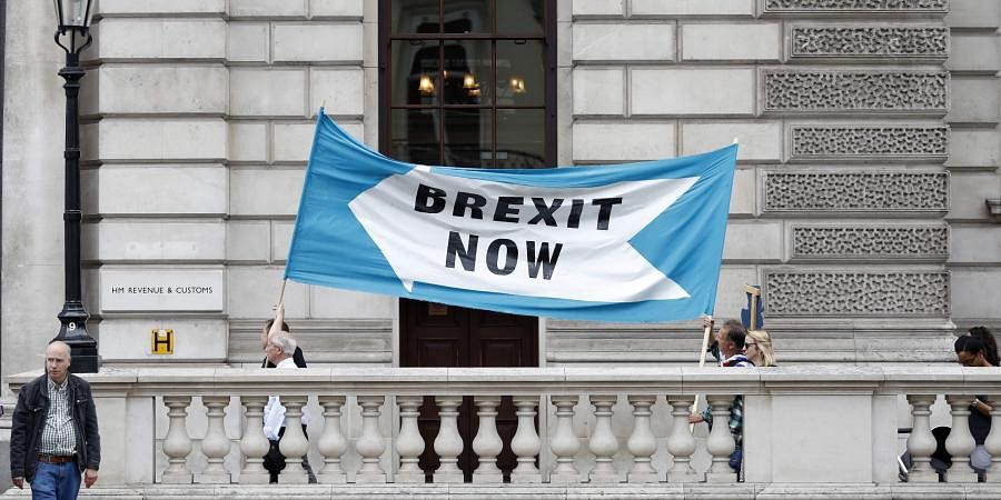 Pro Brexit demonstrators parade their banner past the Treasury building in London.