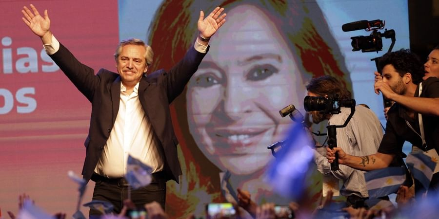 Presidential candidate Alberto Fernández waves to supporters in front of a large image of his running mate, former President Cristina Fernández, after incumbent President Mauricio Macri conceded defeat at the end of election day in Buenos Aires, Argentina, Sunday, Oct. 27, 2019.