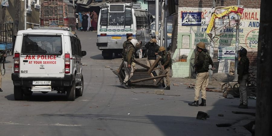 Policemen remove road blocks put up by protesters in Srinagar
