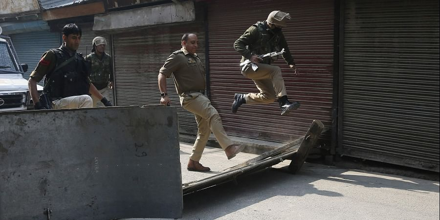 A policeman jumps as his officer kicks to remove a road block put up by protesters in Srinagar