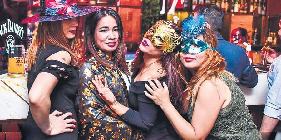 Here, women are seen in costumes at a Halloween party.