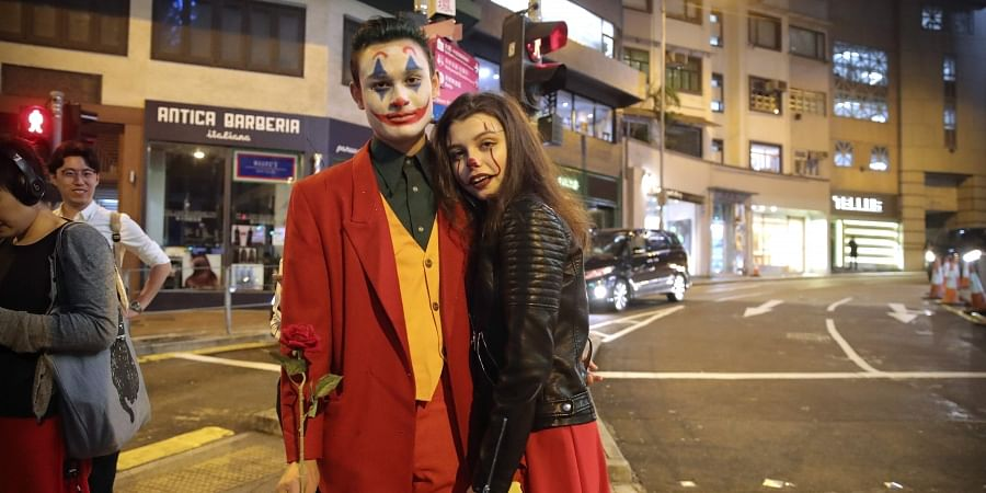 A couple wearing Halloween costumes stand on a street in Hong Kong, Thursday, Oct. 31, 2019.