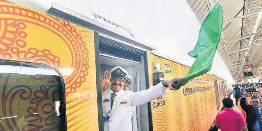 The guard of the Lucknow-Delhi Tejas Express waves the green flag from the Charbagh station in Lucknow.