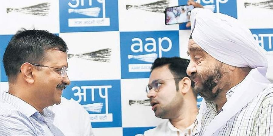Former Congress MLA Parlad Singh Sawhney shakes hands with AAP national convenor Arvind Kejriwal during his induction into the party on Sunday