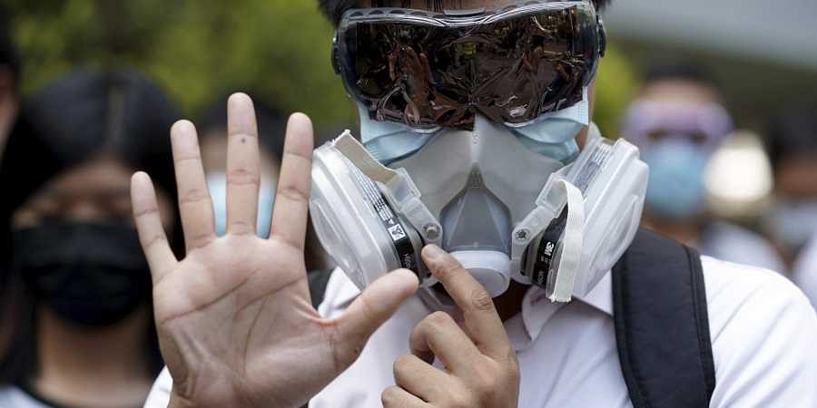 A protester wears a gas mask and holds up his hand to represent the protester's five demands in Hong Kong.