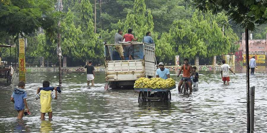 A fruit vendor pushes his cart through floodwaters in Patna