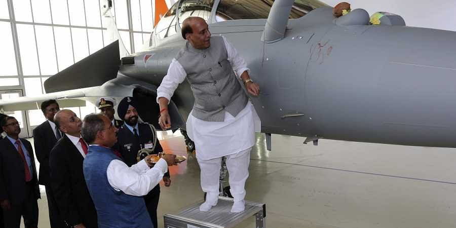 Union Defence Minister Rajnath Singh has a ritual gesture onto a Rafale jet fighter during the handover cermony at the Dassault Aviation plant in France's Merignac on Tuesday, Oct. 8, 2019. France has delivered to India its first Rafale fighter jet from a
