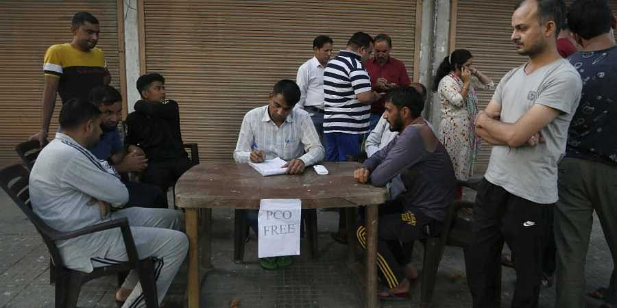 Kashmiris wait to register their numbers before calling from a free public telephone provided by paramilitary soldiers for civilians, outside their base camp in Srinagar