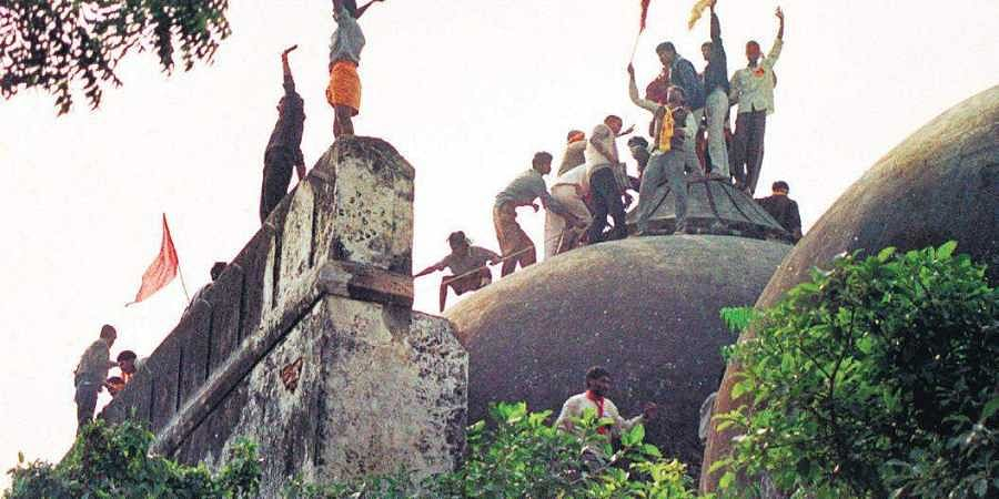 Hindu fundamentalists shout and wave saffron banners as they climb stone walls and demolish the domes of the 16th century Babri Mosque in Ayodhya on December 6, 1992