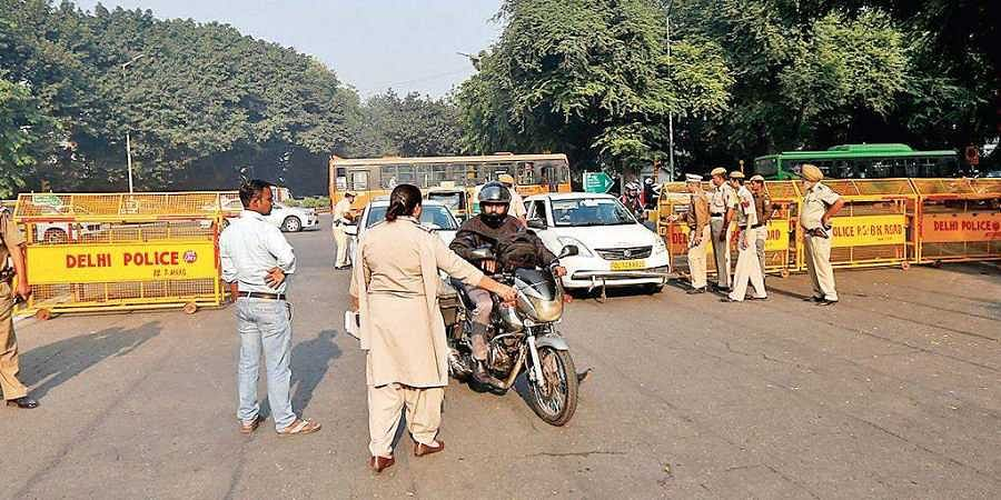 A policewoman stops to check a motorcyclist, as security was beefed up outside the Supreme Court premises after the courts verdict on the Ayodhya land dispute in New Delhi on Saturday.