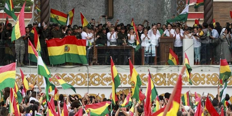 People accompanied by police celebrate the resignation of Bolivian President Evo Morales in Santa Cruz. (Photo | AFP)