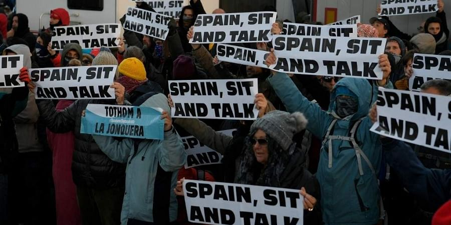 Protesters hold banners reading 'Spain sit and talk' as they block the AP-7 highway at the Spanish-French border in La Jonquera northern Spain, on November 11, 2019 during an action called by Tsunami Democratic movement for civil disobedience actions. Cat