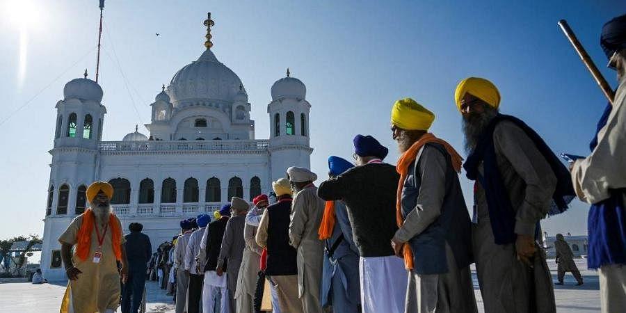 Sikh pilgrims stand in a queue to visit the Shrine of Baba Guru Nanak Dev at Gurdwara Darbar Sahib in Kartarpur.