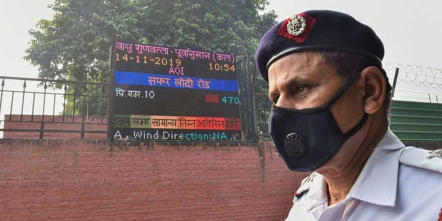 A traffic policeman wearing an anti-pollution mask stands next to a digital board displaying Air Quality Index on the compound wall of a weather observatory at Lodhi Road in New Delhi Wednesday Nov. 13 2019.   (Photo   PTI)