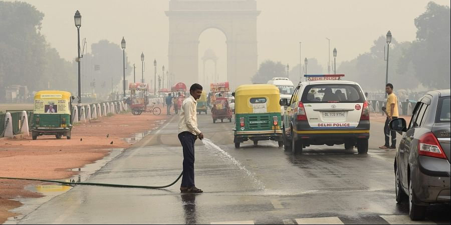 A worker sprays water on a road under heavy smog conditions in New Delhi on November 13 2019. | (Photo | Parveen Negi/EPS)