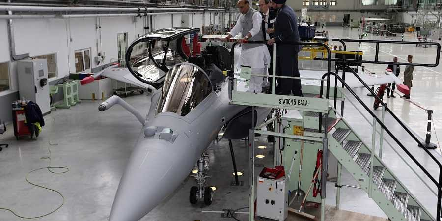 Union Defense Minister Rajnath Singh stands by a Rafale jet fighter in Merignac in southwestern France on Tuesday. Singh formally accepted the first Rafale fighter jet after India had signed a deal with the French government and Dassault Aviation in Septe