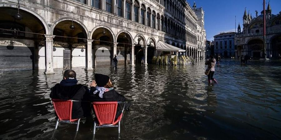 People sit on bistro chairs in the middle of the flooded St. Mark's Square on November 14, 2019 in Venice.
