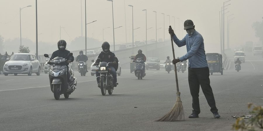 A civic worker wearing an anti-pollution mask sweeps the road amid heavy smog in New Delhi Friday Nov. 15 2019. | (Photo | PTI)